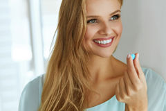 Medicine. Beautiful Smiling Woman Taking Medication Pill. Medicine. Beautiful Smiling Young Woman Holding Blue Vitamin Pill In Hand. Closeup Of Healthy Happy Stock Photos