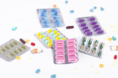 Medicine in blister packs. Colored medicine in blister packs surrounded by pills Stock Image