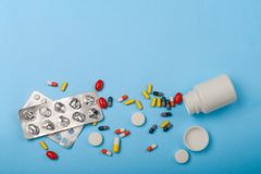 Medicine bottle, blister pack and pills closeup on blue background Stock Photo