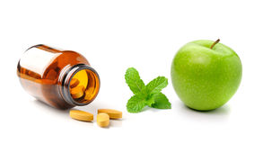 Medicine bottle of brown glass pill apple and mint   on Royalty Free Stock Photography