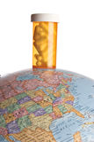 Medicine bottle on an earth globe. On white Stock Image