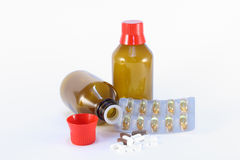 Medicine bottle with pills. One bottle for medical fluids with red cap with different pills and blister Stock Image