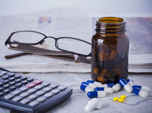 Medicine bottle, pills and financial data Royalty Free Stock Image