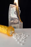 Medicine bottle pills spilling out on table and money burning. Medicine bottle with pills spilling out in large pile onto table and US dollar burning in stock photo