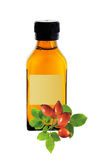 Medicine bottle with yellow syrup and dog-rose isolated on white Royalty Free Stock Photo