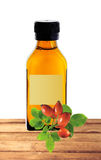 Medicine bottle with yellow syrup and dog-rose on table isolated Royalty Free Stock Photos