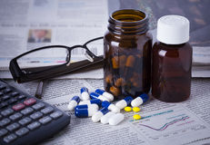 Medicine bottles, pills and financial data Royalty Free Stock Photos