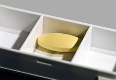 Medicine box with yellow tablet Stock Photo