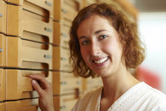 Medicine cabinet. Female pharmacist at medicine cabinet in pharmacy royalty free stock photos