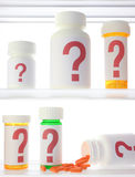 Medicine Cabinet Of Doubt. A few pill bottles in a medicine cabinet, all labeled with red question marks. One bottle is on its side with pills spilling out Stock Photography