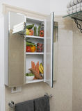 Medicine cabinet with fruits and vegetables. At home medicine cabinet in bathroom filled with nutritious fruits and vegetables royalty free stock photos