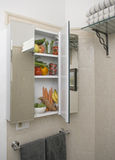 Medicine cabinet with fruits and vegetables. At home medicine cabinet in bathroom filled with ntritious fruits and vegetables stock photography
