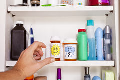 Medicine Cabinet. A male left hand reaches into a medicine cabinet for a pill container Stock Images