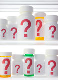 Medicine Cabinet of Worry. Close crop of medicine cabinet shelves filled with pill bottles, each labeled with a red question mark.  Lighting is neutral with Royalty Free Stock Photography