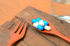 Medicine capsule pill on spoon with fork Royalty Free Stock Photography