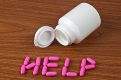 Medicine capsules forming the word HELP Royalty Free Stock Images