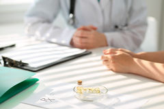 Medicine capsules and pills are lying against the background of a doctor and patient Royalty Free Stock Images