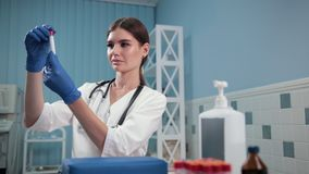 Nurse doctor holding a test tube, carefully examines it. Medicine, clinic, good girl nurse doctor in white medical gown, with stethoscope around his neck, in stock video footage