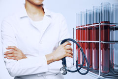 Medicine concept. Female doctor with stethoscope and flasks with red liquid. Medicine concept Stock Image
