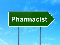 Medicine concept: Pharmacist on road sign background. Medicine concept: Pharmacist on green road highway sign, clear blue sky background, 3D rendering Stock Image