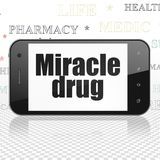 Medicine concept: Smartphone with Miracle Drug on display. Medicine concept: Smartphone with  black text Miracle Drug on display,  Tag Cloud background, 3D Royalty Free Stock Photography