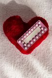 Oral contraceptive pills on red heart. Medicine contraception love and birth control. Oral contraceptive pills on red heart shaped little pillow Royalty Free Stock Photography