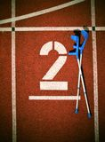 Medicine crutch at number two. Big white track number on red rubber racetrack. Gentle textured running racetracks in small outdoor Royalty Free Stock Images