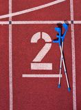 Medicine crutch at number two. Big white track number on red rubber racetrack. Gentle textured running racetracks in small outdoor Royalty Free Stock Image