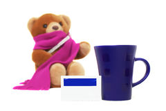 Medicine, a cup and blurred sick Teddy bear. Isolated on white royalty free stock image