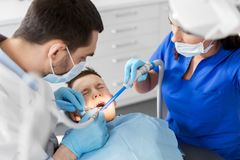 Dentist treating kid teeth at dental clinic. Medicine, dentistry and healthcare concept - dentist and assistant with dental drill and saliva ejector treating kid Stock Photo