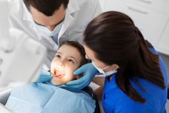Dentist checking for kid teeth at dental clinic. Medicine, dentistry and healthcare concept - dentist with mouth mirror checking for kid patient teeth at dental Royalty Free Stock Images