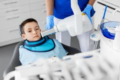 Dentist making x-ray of kid teeth at dental clinic. Medicine, dentistry and healthcare concept - female dentist with x-ray machine scanning kid patient teeth at Stock Photography