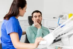 Patient with toothache at dentist office. Medicine, dentistry and healthcare concept - female dentist talking to male patient complaining of toothache at dental Stock Photos