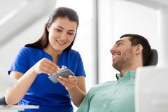 Dentist choosing tooth color for patient at clinic. Medicine, dentistry and healthcare concept - female dentist with tooth color samples choosing shade for male Stock Image