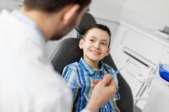 Dentist giving toothbrush to kid patient at clinic. Medicine, dentistry and healthcare concept - male dentist giving toothbrush to kid patient at dental clinic Royalty Free Stock Photography