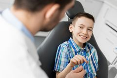 Dentist giving toothbrush to kid patient at clinic. Medicine, dentistry and healthcare concept - male dentist giving toothbrush to kid patient at dental clinic royalty free stock photos