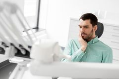 Patient having toothache at dental clinic office. Medicine, dentistry and healthcare concept - male patient suffering from toothache at dental clinic office Stock Image