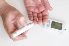 Medicine, diabetes, glycemia, health care and people concept - Close up of man hands using lancet on finger to check high blood su Stock Photography