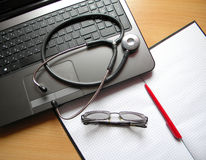 Medicine and diagnostics. Desk Doctor with laptop and stethoscope stock image