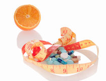 Medicine and diet to lose weight. Concept of diet and medicine. Heap of pills, orange slice and measuring tape with reflection on white background. Focus on stock photography