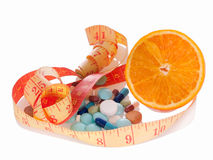 Medicine and diet to lose weight. Concept of diet and medicine. Heap of pills, orange slice and measuring tape with reflection on white background. Focus on royalty free stock images
