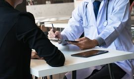 Medicine doctor explain diagnosis to doctor team holding and showing clipboard exploring important document.  royalty free stock photography