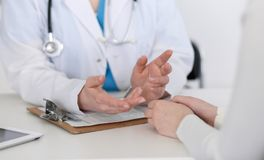 Medicine doctor hand reassuring her female patient closeup. Medicine, comforting  and trusting concept in health care.  Royalty Free Stock Photos