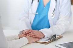 Medicine doctor hand reassuring her female patient closeup. Medicine, comforting  and trusting concept in health care.  Stock Photography
