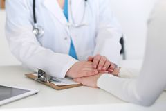 Medicine doctor hand reassuring her female patient closeup. Medicine, comforting  and trusting concept in health care.  Royalty Free Stock Image