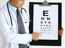 Medicine doctor hold big clipboard pad with eyesight check table Royalty Free Stock Photos