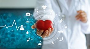 Medicine doctor holding red heart shape and icon medical network. Medicine doctor holding red heart shape in hand and icon medical network connection with modern royalty free stock photo