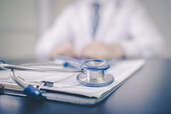 Medicine doctor`s working table. Focus on stethoscope Royalty Free Stock Photography