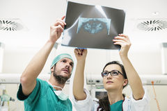 Medicine doctor showing something to her male colleague on x-ray. Image. Healthcare and medical concept Royalty Free Stock Photos