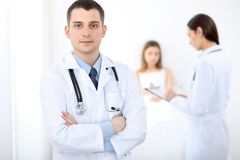 Medicine doctor standing and smiling on the background with patient in the bed royalty free stock photography